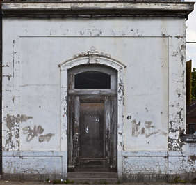 door wood arch ornate old worn building facade house