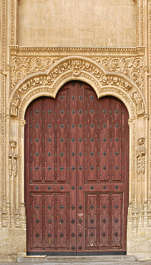 door wood planks ornate church studded armored arch