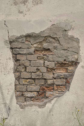 plaster damaged bricks exposed